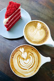 Cup of latte art coffee and cake. On wood table royalty free stock images