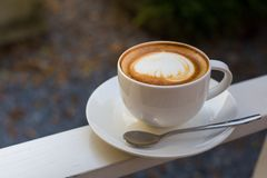 A cup of a latte art coffee with little spoon on white table Royalty Free Stock Photography