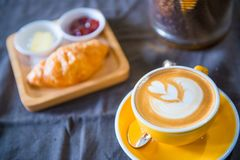 A cup of latte art with a croissant in cafe stock images