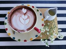 Cup of latte art serve on the wooden board with flower on the black and white strip tablecloth background. On the top view Royalty Free Stock Photos
