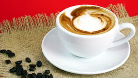 Cup of latte, cappuccino or espresso coffee with milk put on the red background with dark roasted coffee beans Stock Images
