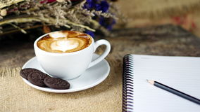 Cup of latte, cappuccino or espresso coffee with milk put on a wood table with dark roasted coffee beans. A cup of latte, cappuccino or espresso coffee with milk Stock Photography