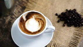 Cup of latte, cappuccino or espresso coffee with milk put on a wood table with dark roasted coffee beans. A cup of latte, cappuccino or espresso coffee with milk Stock Photo