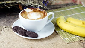 Cup of latte, cappuccino or espresso coffee with milk put on a wood table with dark roasted coffee beans Royalty Free Stock Images