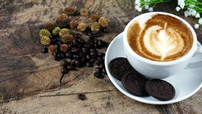 Cup of latte, cappuccino or espresso coffee with milk put on a wood table with dark roasted coffee beans Royalty Free Stock Photography