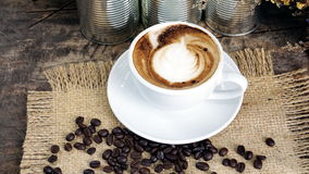 Cup of latte, cappuccino or espresso coffee with milk put on a wood table with dark roasted coffee beans Stock Photos