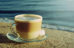 Cup of latte or cappuccino by the sea. With retro filter effect Royalty Free Stock Photos