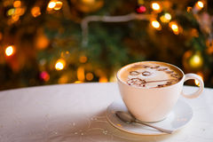 Cup of latte coffee. With Christmas lights shining in background royalty free stock photo