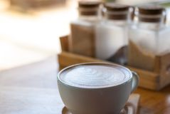 A cup of latte coffee with art foammilk placed on wooden tray wi stock images