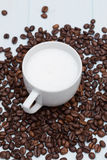 Cup of latte coffee with beans. On wood table Royalty Free Stock Photo