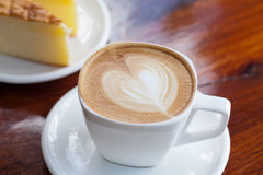 Cup of latte coffee with cake. On table Stock Photography