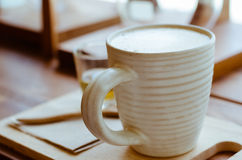 Cup of Latte Coffee In Cozy Coffee Shop. A cup of hot latte coffee on wood table in cozy coffee shop Stock Images