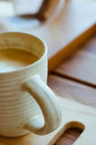 Cup of Latte Coffee In Cozy Coffee Shop. A cup of hot latte coffee on wood table in cozy coffee shop Royalty Free Stock Image