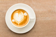 Cup of latte coffee with heart drawing on wooden background stock photography