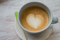 A cup of latte coffee with heart pattern in a white cup on white marble background and green sugar stick. A cup of coffee with heart pattern in a white cup on Stock Photos