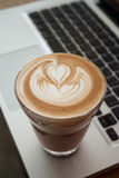 A Cup of latte coffee on laptop keyboard. 