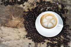 Cup of latte coffee with milk put on a wood table with dark roasted coffee beans. A cup of latte, cappuccino or espresso coffee with milk put on a wood table Royalty Free Stock Image
