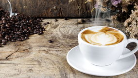 Cup of latte coffee with milk put on a wood table with dark roasted coffee beans. A cup of latte, cappuccino or espresso coffee with milk put on a wood table Royalty Free Stock Photography