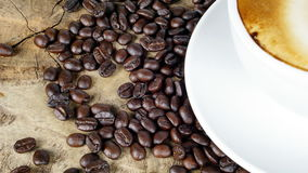 Cup of latte coffee with milk put on a wood table with dark roasted coffee beans. A cup of latte, cappuccino or espresso coffee with milk put on a wood table Royalty Free Stock Photo