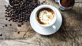 Cup of latte coffee with milk put on a wood table with dark roasted coffee beans. A cup of latte, cappuccino or espresso coffee with milk put on a wood table Royalty Free Stock Images