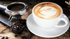 Cup of latte coffee with milk put on a wood table with dark roasted coffee beans. A cup of latte, cappuccino or espresso coffee with milk put on a wood table Stock Images