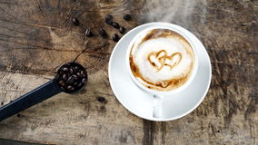 Cup of latte coffee with milk put on a wood table with dark roasted coffee beans. A cup of latte, cappuccino or espresso coffee with milk put on a wood table Royalty Free Stock Photos