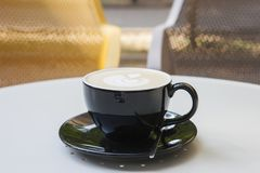 A cup of latte coffee on a table in a cafe. On a blurred background a park is seen royalty free stock images