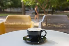 A cup of latte coffee on a table in a cafe. On a blurred background a park is seen royalty free stock photos