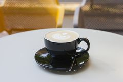 A cup of latte coffee on a table in a cafe. On a blurred background a park is seen stock photos