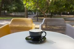 A cup of latte coffee on a table in a cafe. On a blurred background a park is seen royalty free stock image