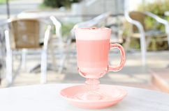 A cup of latte coral color on the table of the summer patio royalty free stock photos