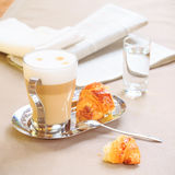 Cup of latte with croissant. Tablecloth background with newspape Royalty Free Stock Photography