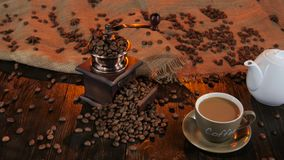 Cup with latte and white teapot on wooden table. Studio stock footage