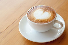 A cup of latte on the wood table Stock Image