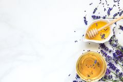 Cup of lavender tea with honey and fresh flowers over white marble table. herbal drink. top view Royalty Free Stock Images