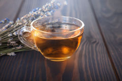 Cup of lavender tea and lavender flowers. Cup of lavender tea and lavender flowers on a wooden table stock photography