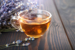 Cup of lavender tea and lavender flowers. Cup of lavender tea and lavender flowers on a wooden table royalty free stock photo