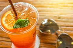 Cup of the lemon ice tea with orange and mint on top on the brown bark beautiful texture background with warm light. Decorated with sunglasses stock photos