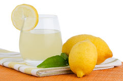 Cup of lemon juice and fresh lemons Royalty Free Stock Photos