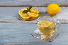 Cup of lemon tea. Lemon tea in a glass cup on blue rustic background Royalty Free Stock Photography