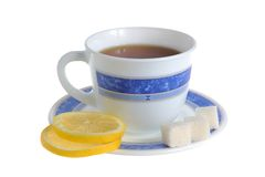 A cup of lemon tea and two slices of lemon, refined sugar on sau Stock Photography