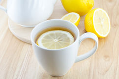 Cup of lemon tea on wooden table. Cup of lemon tea and lemon slice on wooden table Royalty Free Stock Images
