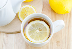 Cup of lemon tea on wooden table. Cup of lemon tea and lemon slice on wooden table Stock Photography