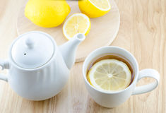 Cup of lemon tea on wooden table. Cup of lemon tea and lemon slice on wooden table Royalty Free Stock Image