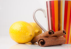 Cup with lemons and cinnamon. Cup with two lemons and cinnamon on white Stock Image