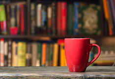 Cup in a library Royalty Free Stock Images
