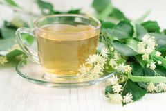 Cup of linden tea. Cup of tea and linden flowers on wooden background royalty free stock photo