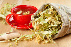 Cup of linden tea and flowers in canvas bag Royalty Free Stock Photo