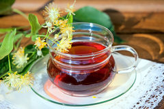 Cup with linden tea and flowers on wooden table Royalty Free Stock Photo