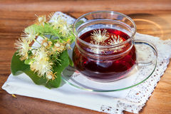 Cup with linden tea and flowers on wooden table Stock Images